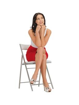 Mulher feliz em um vestido em uma cadeira