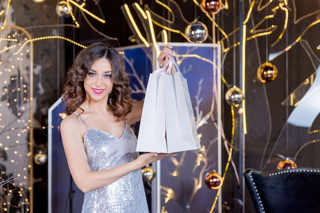 Mulher feliz em um vestido preto com sacolas de compras sobre as luzes da árvore de natal