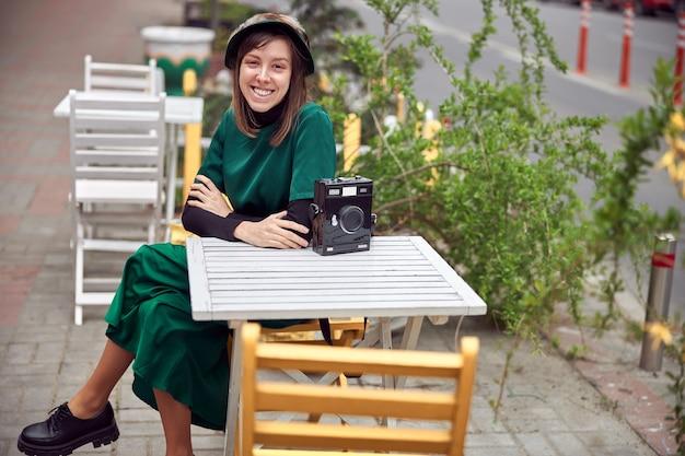 Mulher feliz em um vestido verde em uma cidade urbana está sentada perto de um café