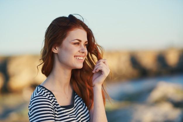 Mulher feliz em uma camiseta listrada cabelo ruivo sorriso de modelo