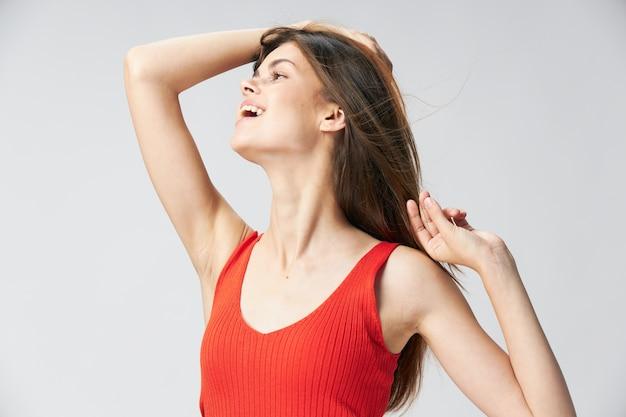 Mulher feliz em uma camiseta vermelha toca o cabelo da cabeça com a mão e olha para o lado