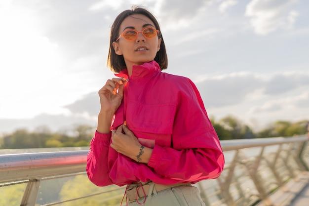 Mulher feliz em uma elegante jaqueta esportiva rosa caminhando de manhã cedo