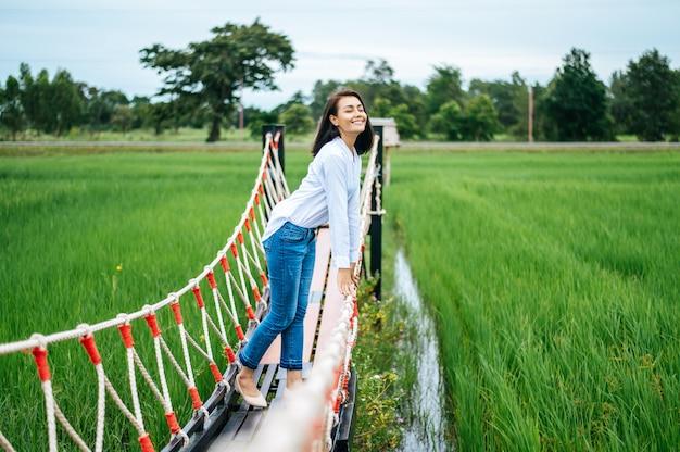 Mulher feliz em uma ponte de madeira em um prado verde em um dia ensolarado