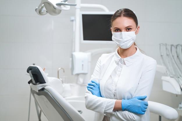 Mulher feliz em uniforme madical e luvas estéreis e máscara está esperando por pacientes em um escritório moderno.