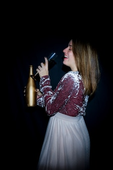 Mulher feliz, em, vestido, bebendo, champanhe, de, vidro
