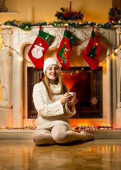 Mulher feliz em vestido de malha sentada no chão ao lado da lareira com uma xícara de chá