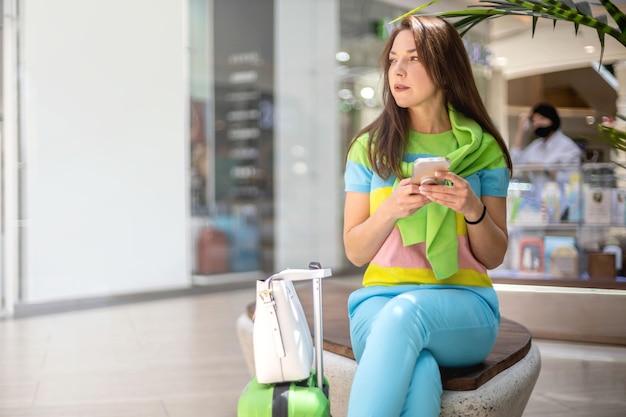 Mulher feliz em viagens com roupas de verão brilhantes, conversando sobre navegação na internet na área de compras duty free