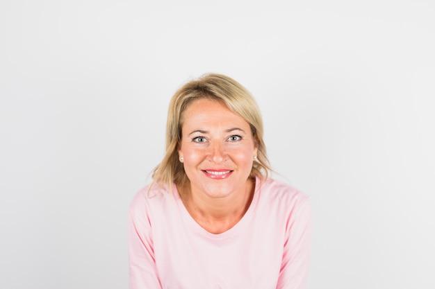 Mulher feliz envelhecida na blusa rosa