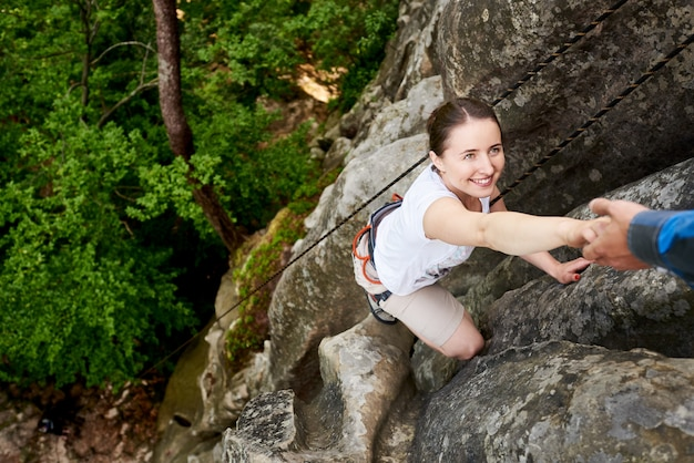 Mulher feliz escalada rocha caminhadas ao ar livre. alpinista despreocupada, sorrindo sua amiga. homem ajudando a escalar rocha