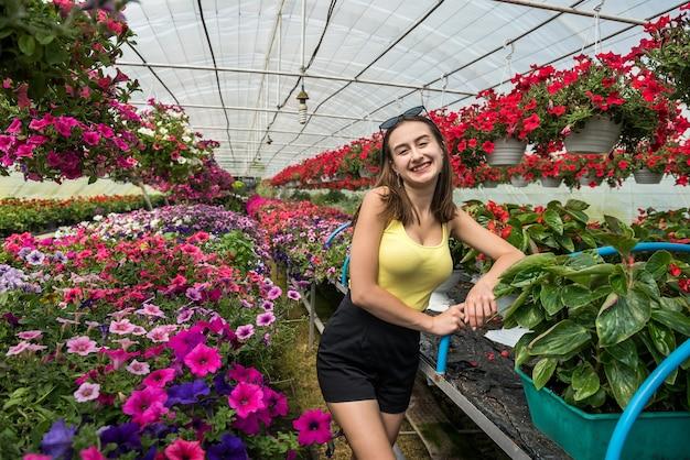 Mulher feliz escolhe flores em uma estufa. botânica
