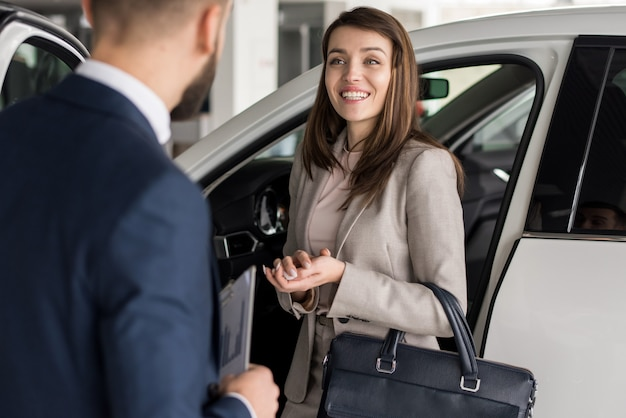Mulher feliz escolhendo carro no showroom
