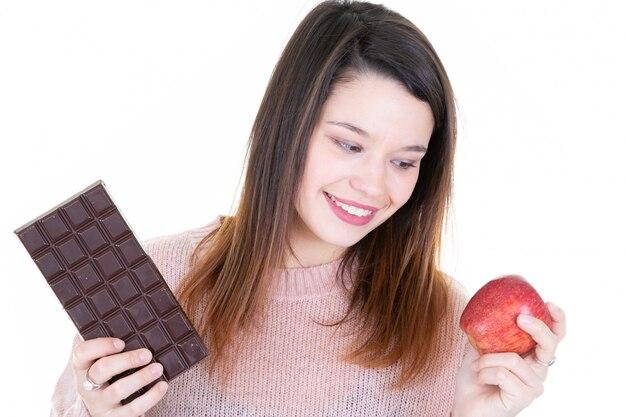 Mulher feliz escolhendo entre chocolate escuro e fruta maçã vermelha sobre branco