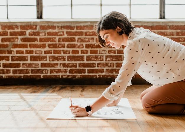 Mulher feliz escrevendo em um papel gráfico branco no chão