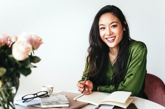 Mulher feliz escrevendo um diário em seu escritório