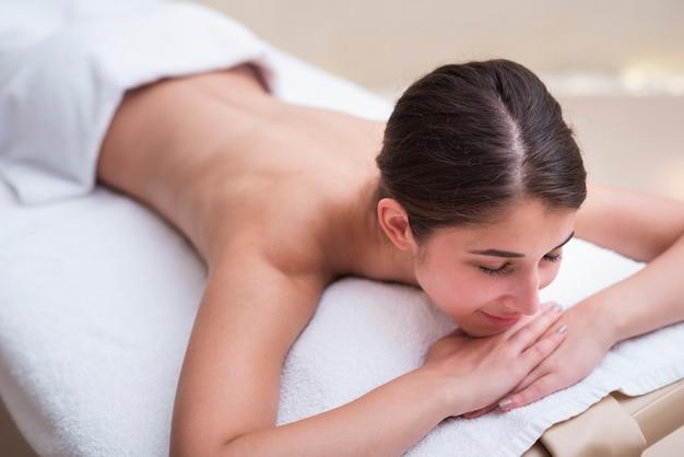 Mulher feliz, esperando a massagem no spa