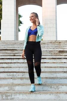 Mulher feliz esportes jovem caminhando por etapas ao ar livre, ouvindo música com fones de ouvido.