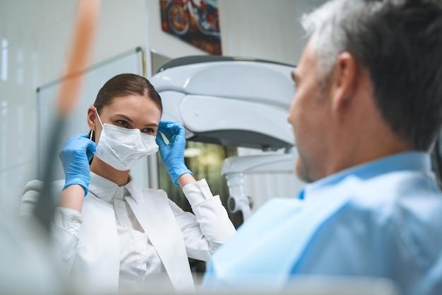 Mulher feliz está usando máscara e luvas esterilizadas enquanto trata de problemas dentais masculinos no consultório
