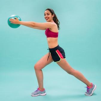 Mulher feliz esticando e treinando com uma bola
