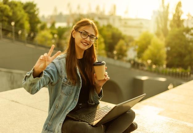 Mulher feliz estudante moderna em uma jaqueta jeans, sentado nas escadas com o laptop, xícara de café e mostra um gesto v ao ar livre. ensino à distância. conceito moderno da juventude.