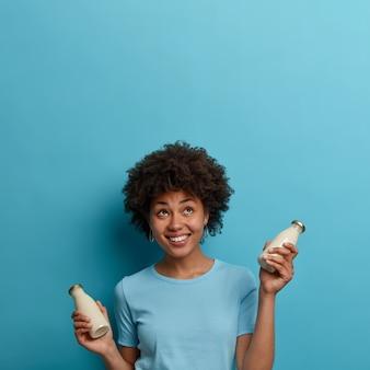 Mulher feliz étnica encaracolada bebe bebida sem lactose, segura uma garrafa de leite de amêndoa ou coco, olha para cima, sorri positivamente, isolada sobre a parede azul, copie o espaço para sua informação