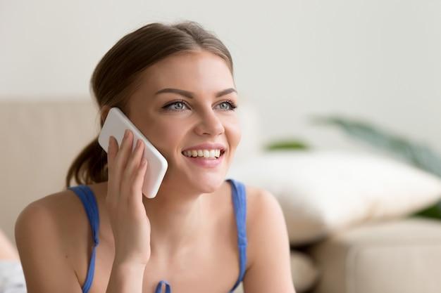 Mulher feliz falando no celular em casa