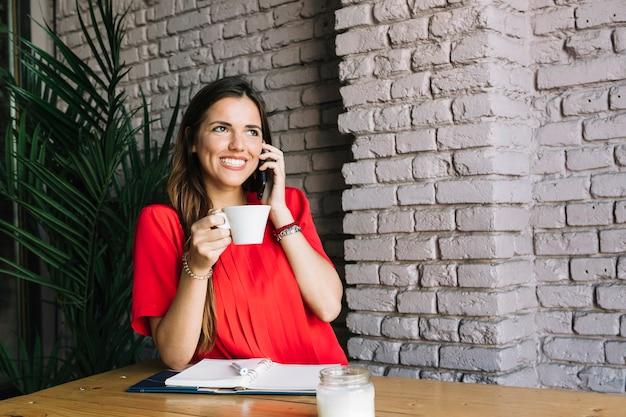 Mulher feliz falando no celular enquanto bebe café