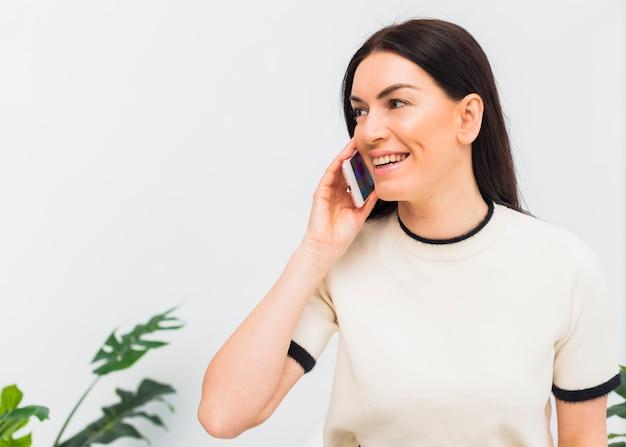 Mulher feliz, falando por telefone