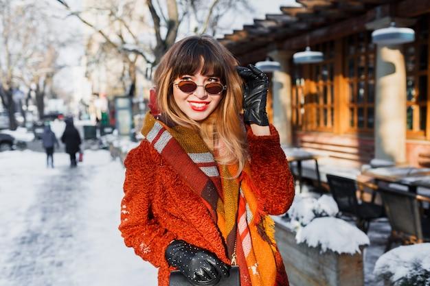 Mulher feliz fascinante com óculos retrô posando ao ar livre