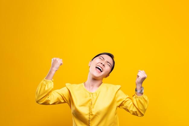 Mulher feliz faz gesto vencedor isolado sobre parede amarela