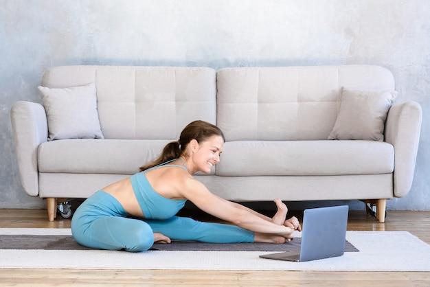 Mulher feliz fazendo esportes em casa online usando laptop enquanto pratica alongamento