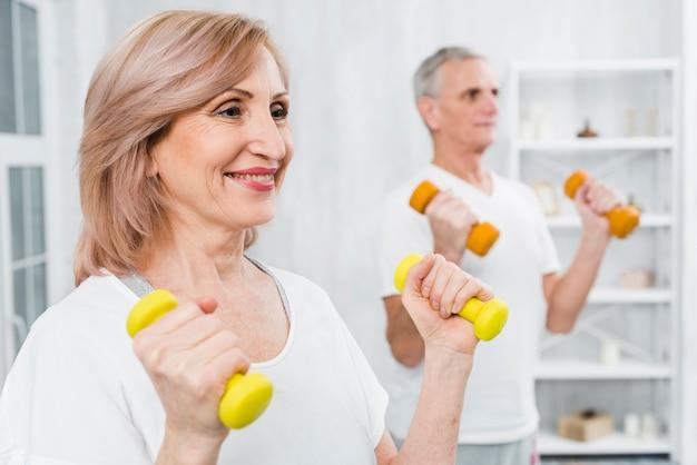 Mulher feliz, fazendo, exercício, com, dumbbells