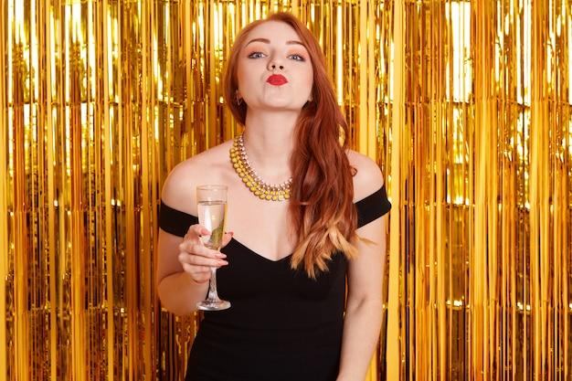 Mulher feliz fazendo gesto de beijo enquanto segura a taça de vinho, usando um vestido preto e colar