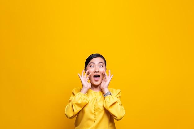 Mulher feliz fazendo grito gesto isolado sobre parede amarela