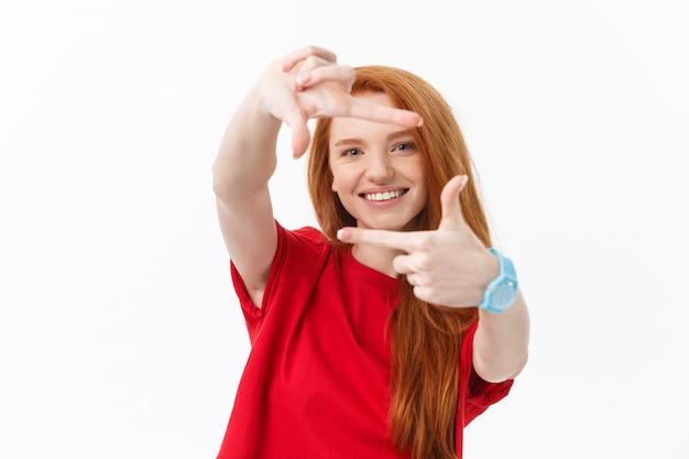 Mulher feliz fazendo moldura com os dedos isolados no branco