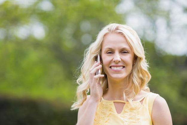 Mulher feliz fazendo um telefonema fora