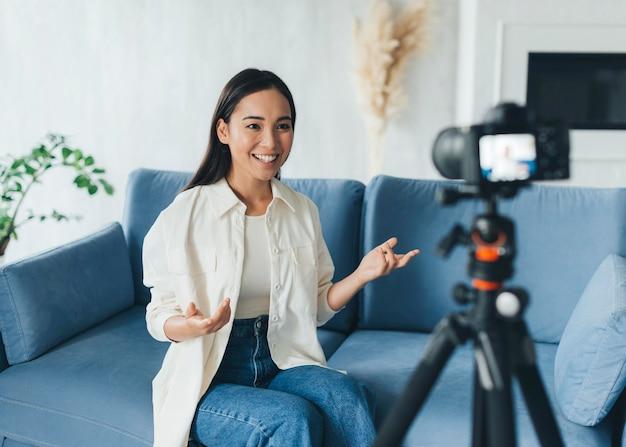 Mulher feliz fazendo um vlog em casa
