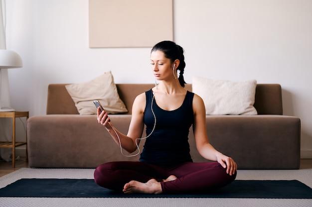 Mulher feliz fazendo yoga em casa e ouvindo música no telefone