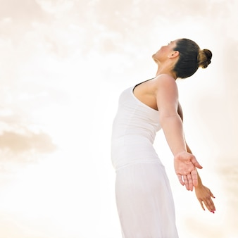 Mulher feliz fazendo yoga sob o sol