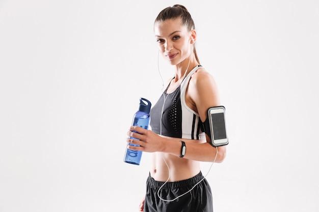 Mulher feliz fitness em fones de ouvido em pé e segurando a garrafa de água