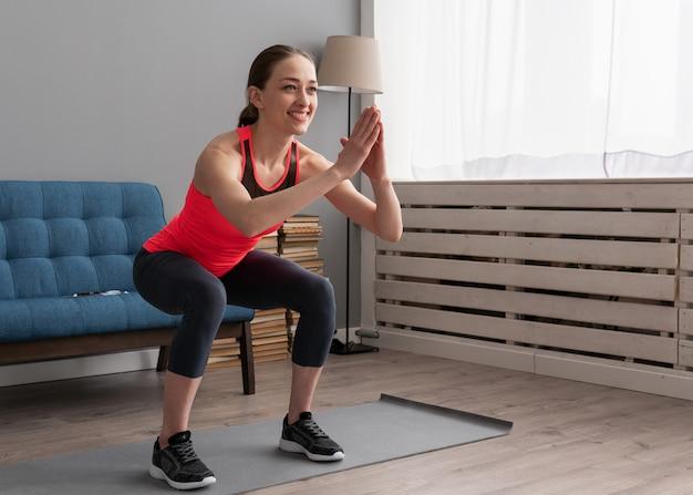 Mulher feliz fitness fazendo exercício de agachamento em casa
