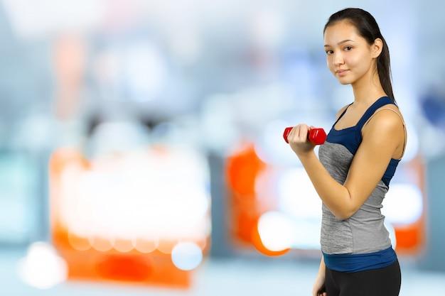 Mulher feliz fitness levantando halteres