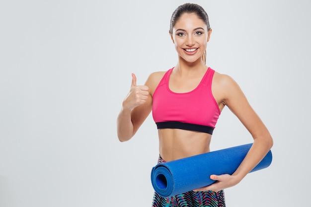 Mulher feliz fitness segurando o tapete de ioga e mostrando o polegar