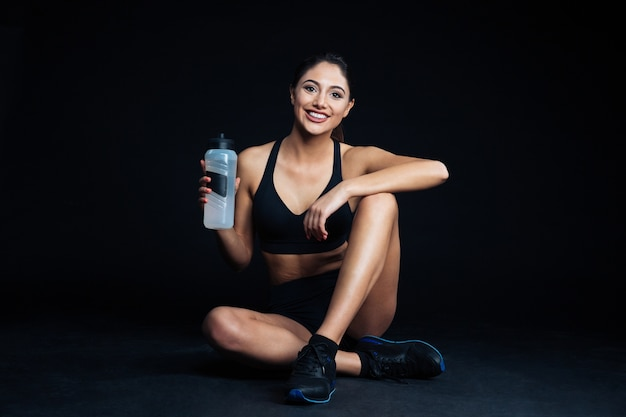 Mulher feliz fitness sentada no chão com uma garrafa de água no fundo preto