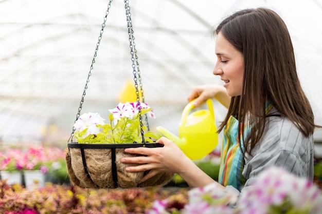 Mulher feliz, florista, com avental, sorrindo, cultivando flores em flor em um canteiro de flores pendurado