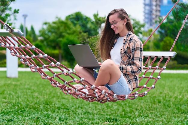Mulher feliz freelancer relaxante numa rede