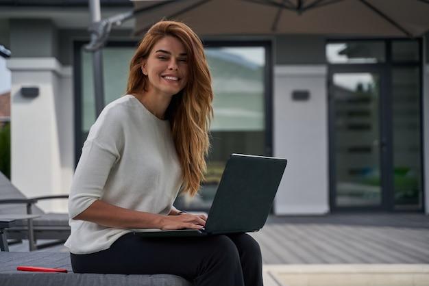 Mulher feliz gengibre olhando para a câmera enquanto usa seu laptop na beira da piscina em um dia ensolarado. trabalho freelance em seus apartamentos perto da piscina. conceito de tecnologias