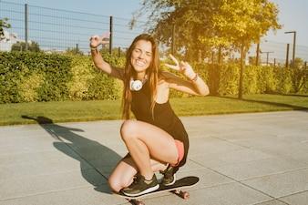 Mulher feliz, gesticule, sinal paz, enquanto, skateboarding, parque