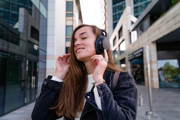 Mulher feliz gosta de música em fones de ouvido sem fio enquanto caminhava pela cidade
