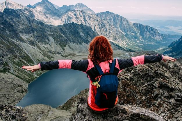 Mulher feliz gosta de vista do lago nas montanhas de verão