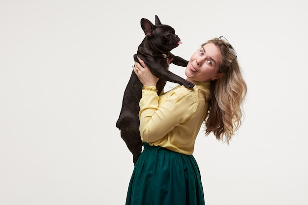 Mulher feliz hipster brincando com bulldog francês na parede branca